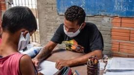 Voluntário dá aula para crianças entre escombros de casas demolidas